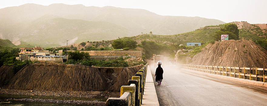 A woman crosses a bridge in a rural area of Pakistan [Pixabay]